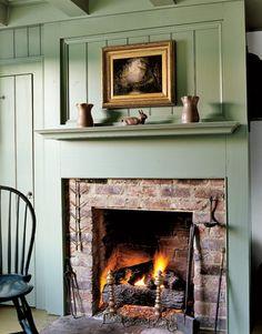 Un mur de sauge verte soulevé panneau révèle une cheminée en briques simple dans cette maison du début du 19ème siècle.  Poterie antique est affiché sur la cheminée.