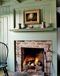 A sage green raised panel wall reveals a simple brick fireplace in this early-19th-century home. Antique pottery is displayed on the mantel.