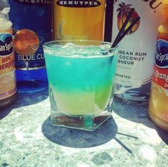 ARUBA PARADISE ~ 1 oz. (30ml) Malibu Coconut Rum, 1/2 oz. (15ml) Banana Liqueur, 1 oz. (30ml) Orange Juice, 1 oz. (30ml) Pineapple Juice, Splash of Blue Curacao