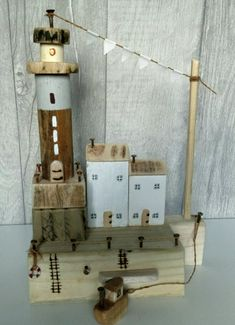 Made entirely from reclaimed wood, metal and driftwood, this adorable Lighthouse and Cottage scene features 2 sail white cottages side by side next to a tall wood and grey lighthouse. Bunting trails from the Lighthouse to a post and the scene is protected with metal harbour posts