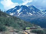 Skagway, Alaska to White Pass, British Columbia.  There is a famous narrow gauge railroad that follows the path of the Alaskan Goldrush in Skagway. The tiny trains creep along the cliffs past all sorts of gorgeous scenery while you learn about the Gold Rush. Good tour for the whole family.