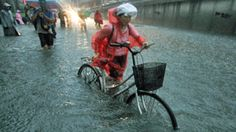 A Beijing resident pushes her bicycle on a flooded street amid heavy   AP  21/07/2012
