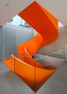 A fluorescent orange staircase spirals up through the centre of this house in Peru