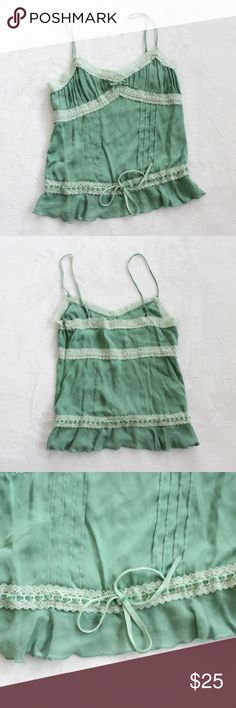 """Bebe Green Lace Trim Camisole Tank Top Women's Bebe Green Lace Trim Camisole Tank Top Women's Size Small Strap Sleeveless V- neckline Sleeveless with adjustable straps Tie at waist Intended to hit at or right above natural waistline- please see measurements for accurate sizing Great Condition! Clean- no stains, tears, or snags noted. Gently worn. Pics show accuracy of condition! From a pet & smoke free home  Measurements (approx):  length 16"""" pit-to-pit 13"""" waist 24"""" Fabric:  91% Silk 9%…"""