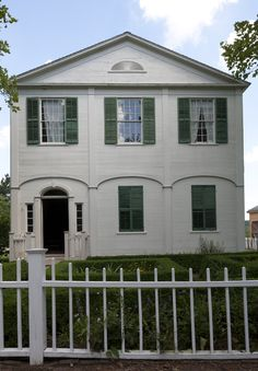 """MacKay Homestead, built 1814, Caledonia, NY. By 1814, MacKay had prospered sufficiently to build the two-story brick-lined house that now looks out across the Genesee Country Village square. The American version of the modified Georgian style popular in the period is termed """"Federal"""" or """"Post-Colonial."""" Its lightened and attenuated forms are seen in the architectural detailing of the MacKay house with its gable end turned toward the road."""