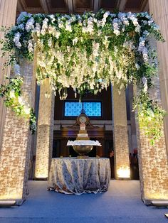 This is a photo of our custom built chuppah with our suspended floral! Within this photo you will find our golden alloy linen upholstered in each column. We love to be creative and innovative!