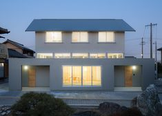 Japanese house made up of bulky rectilinear base with house-shaped block on top