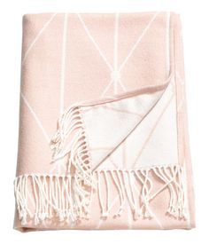 Light pink. Throw in soft jacquard-weave fabric with fringe at short sides.