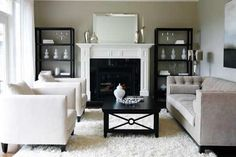 living rooms - Benjamin Moore - Revere Pewter - grey gray fireplace gray tufted sofa white chairs flokati rug black mirrored cocktail table bookshelves