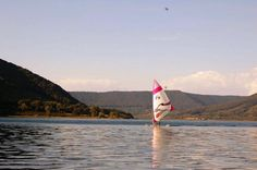 Windsurfer in August exercising, and then, in September, with the wind, will skyte on the water