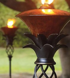 Grace your walkways or patio with a warm glow from the charming Pineapple Torches, with an antique brass reservoir filled with a sunken opening to minimize spills.