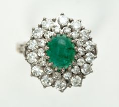 EMERALD AND DIAMOND RING. European, 20th century. Platinum setting containing oval cabochon emerald surrounded by 28 round diamonds approximately 2.0ct tw, E-F color, VVS clarity. 14k white gold Fingermate shank. Sold at Garth's Auctions on December 9, 2015 for $1,320.