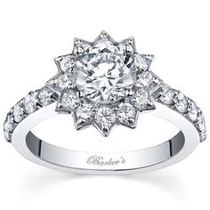 This bold diamond engagement ring features an elegant star design sporting an all-prong setting with a round diamond center stone encircled in a starburst halo of diamonds. The shared prong-set diamon