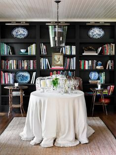 skirted round table, dark bookshelves