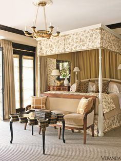 """We also created a coffered ceiling lined in leather for the library, which alludes to a gentleman's club in Mayfair,"" says Powers. ""The house has a masculine but warm ambience. Sandra doesn't like frilly interiors—she prefers a tailored look. I did suggest something softer for the master bedroom. Hence, the extensive use of English toile."" Baluster lamp, Visual Comfort. Walls and customized Baker bed in Colefax & Fowler toile. Pillows in Clarence House leopard velvet. Bed linens, ..."