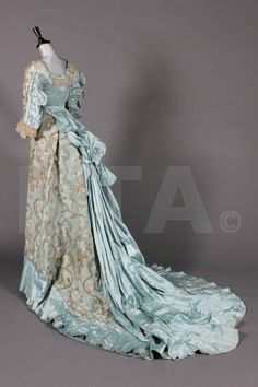 Back: An 1890s fancy dress gown, incorporating 1730s ice blue brocaded satin, comprising bodice with deep curved front waist, cut high at the back with short tails, ruffled and gathered blue satin outside sleeves, the front skirt entirely of 18th century brocade, pleated blue satin band to hem, long blue satin train to rear skirt. via Kerry Taylor Auctions