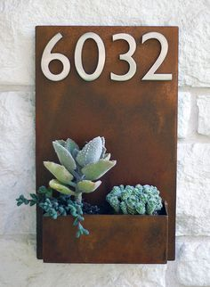 A modern planter that doubles as an address plaque.