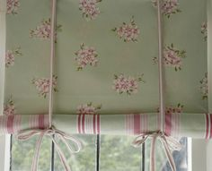 Two different patterns of fabric sewn together to make a shade - rolled up from the bottom and tied. Swedish shades