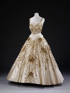 Evening Dress worn by Queen Elizabeth II | Norman Hartnell | c. 1957  Lavish gold and white beadwork encrusts this ivory evening dress worn by Queen Elizabeth II on a state visit to Paris in 1957. Victoria and Albert Museum