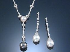 A PAIR OF CULTURED PEARL & DIAMOND EAR PENDANTS & A PENDANT NECKLACE, SCHOEFFEL.  The necklace designed at the front as a series of stylised foliate motifs millegrain-set with brilliant-cut diamonds, centring on a cultured pearl of white tint & suspending a cultured pearl of grey tint, to a fine chain, signed Schoeffel; accompanied by a pair of ear pendants, each designed as a line of alternating navette-shaped & brilliant-cut diamonds, suspending a capped cultured pearl drop, signed…