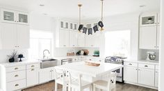 @whitelanedecor #whitelanedecor All white kitchen, brass pendants, stainless steel farm sink, ikea bar stools, cabinets all the way to the ceiling, double stacked kitchen cabinets, glass upper cabinets.