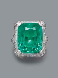 AN ART DECO EMERALD AND DIAMOND RING  The cushion-shaped emerald weighing 20.72 carats within baguette and single-cut diamond surround to diamond fleur-de-lys shaped shoulders and plain hoop, circa 1935
