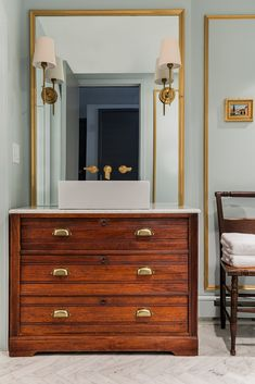 dresser, brass pulls, brass framed mirror and sconces - nice to add a touch of modern, with the square vessel sink