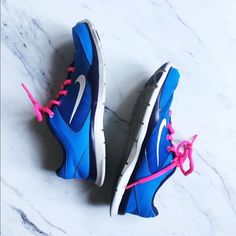 Pink and Blue Nike Training Tennis Shoes Definitely worn in but have a lot of life left in them. Pink laces, blue body, white base. Some normal wear and tear, but generally great condition! Would be almost perfect with a cleaning. Nike Shoes Sneakers