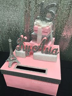 This card box is a work of art and absolutely gorgeous! A real show stopper for your sweet 16! It doubles as a centerpiece for the VIP table. Not having a paris theme? Thats ok! Ask us about other themes. This large box is available in a 12 and 14 size and features a triple stack of gift boxes adorned with a beautiful bow and rhinestone topper complete with a glittered 16! Your name is stacked on a rhinestone riser and an 8 metal 3d Eiffel tower sets the stage for the perfect paris theme…