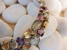Collar artesanal de plata, elaborado artesanalmente engarzando en un exquisito diseño asimetrico gemas de Aguamarinas, Amatistas y Cuarzo Cetrino facetadas en Jaipur, India