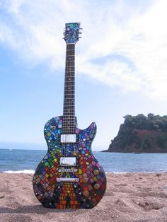 Matthew Bellamy's guitar (MUSE) put on eBay in in September was bought £8,100. If you did not know this offer, The Resistance Mosaic Artwork is a guitar which was for sell to benefit The Helen Foundation, run by the members of the band Muse in memory of their friend Helen Kirk. Given by Mansons — which also sign Matt's guitars, and nicely decorated by the artist Michelle Wilcox, this autographed guitar is mysterious because there are not such informations about its characteristics.