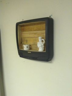 Repurposed shelf made from an old television set. I saw so many of these going into the dumpster that I had to try something.... Used recycled pallet wood for the backing. The remote doesn't work anymore but it's still kind of cool.