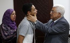 Palestinian President Mahmoud Abbas checks the face of Tariq Khdeir as he meets the family of Palestinian teen Mohammed Abu Khudeir in the West Bank city of Ramallah July 7, 2014. An Israeli judge released from jail and placed under house arrest Tariq Khdeir, the 15-year-old American of Palestinian descent whose apparent beating by Israeli police in East Jerusalem has drawn U.S. concern. Khdeir from Tampa, Florida, is a cousin of Mohammed Abu Khudeir, 16, whose     REUTERS/Mohamad Torokman