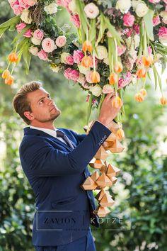 Zavion Kotze admiring his work for this wonderful wedding.Beautiful having arrangement, suspended floral arrangement, hanging flowers, tulips, roses, gold, white, green, floral art, incredible wedding. best wedding, wedding day.