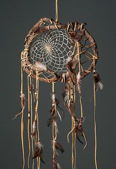 "Wanderer Dream Catcher -   The Frame is made of Grape Vine and detailed with glass and wood beads, goat hide and feathers. Webbed with sinew. Each piece will vary in size. Approx. 10"" x 12""  - http://www.indianvillagemall.com/dreamcatchers/twigdreamcatchers.html"