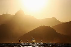 Men's 470 class #sailing return to shore under a #sunset after a race in #brazil, beneath the statue of Christ in #rio2016 in phlow