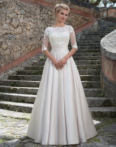 This Grace Kelly inspired ball gown features a beaded Sabrina lace bodice, satin cummerbund, and a full skirt with pockets. The stretch beaded lace jacket completes this refined look.