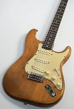 Well, here we have a wonderful 1961 Fender Stratocaster. We believe it started its life as Dakota Red, and has been refinished once in blue and then stripped. Neck pocket and cavities show both colors, with the neck pickup cavity having tape with blue paint on top of it and red underneath. We als...