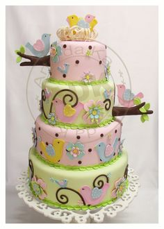 4 tier cake with pink and green fondant and other embellishments
