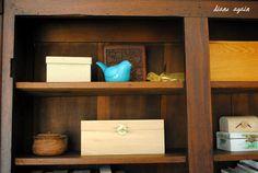 living room. black walnut cupboard shelf. turquoise bird. boxes.