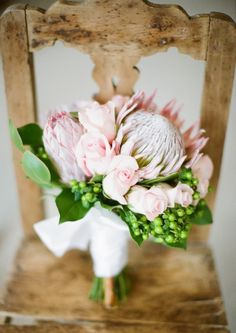 Love this photo of the bride's bouquet on a simple wooden chair. The light pink roses and protea graced with green hypericum berries, make the perfect bouquet for a spring wedding! Protea Wedding, Floral Wedding, Wedding Flowers, Wedding Colors, Lace Wedding, Wedding Dresses, Deco Floral, Floral Design, Love Flowers