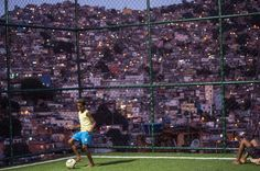 A boy plays with a football as the Netherlands and Spain play FIFA World Cup 2014 football match, at the Rocinha shantytown in Rio de Janeiro, Brazil, on June 13, 2014. (AFP PHOTO / YASUYOSHI CHIBA)