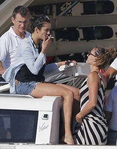 Hanging out: Nina Dobrev smokes a cigarette on her luxury yacht in hotpants and a denim sh...