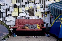 Umbrella Revolution Hong Kong, A demonstrator sleeps on a couch outside the Central Government Offices in the Admiralty district of Hong Kong, China, on Tuesday, Oct. 28, 2014. Hong Kong's pro-democracy protesters will this evening mark a month since police used tear gas in a failed attempt to disperse them, as leaders debate whether to reopen discussions with the government. Photographer: Brent Lewin/Bloomberg via Getty Images