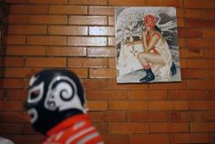 A photo of Mexican lucha libre wrestler Estrella Dorada (Spanish for Golden Star), taken in 1989, hangs on a wall behind her husband at her house on the outskirts of Mexico City, September 28, 2011.  REUTERS/Carlos Jasso