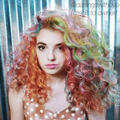 curly orange hair with green blue pink streaks