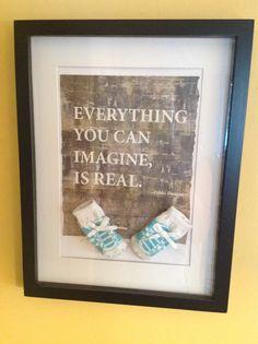 Framed baby socks.  Background poster from Koto-living magazine