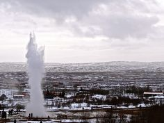 'Tourists look on as the amazing Strokkur geyser erupts in front of them in Iceland.'