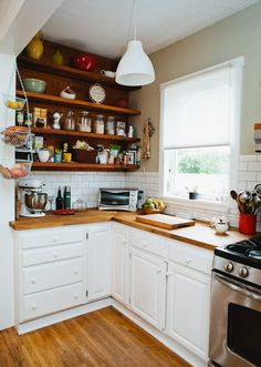 So cozy. This has all my favorite things. Like butchers block countertops. And white cabinets and subway tile with contrasting grout. And those cute little hanging vegetable things. And a kitchenaid mixer and open shelving.