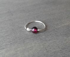 Simple and organic, this small hoop earring will captivate with the intense color of its garnet.